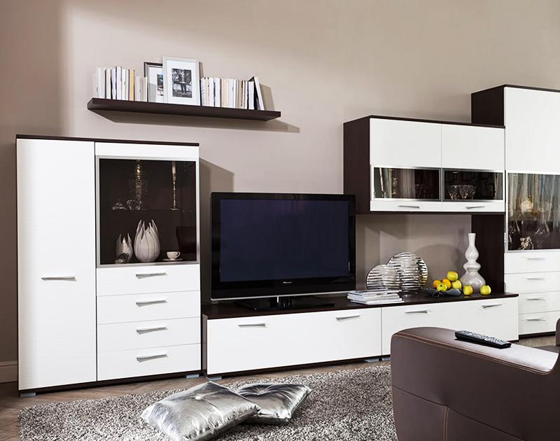 В гостиной важно оборудовать зону для хранения книг и некоторых вещей, а также для телевизора, если он есть в квартире. Самый простой способ – покупка шкафа-стенки. Отдавайте предпочтение современным моделям из белого или светло-коричневого дерева, без ручек и лишней фурнитуры