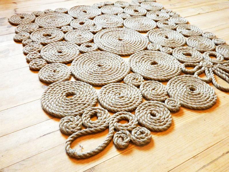 Если вы хотите сделать большой коврик на половину комнаты, заранее сплетите множество маленьких кружков из джута и соедините их с помощью больших нитей или приклеивая джутовые «пятаки» друг к другу