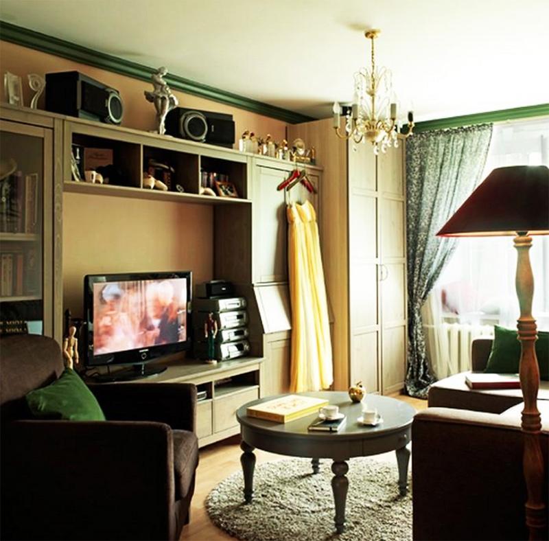 Окно в гостиной задрапировано зелёными портьерами с неярким цветочным принтом