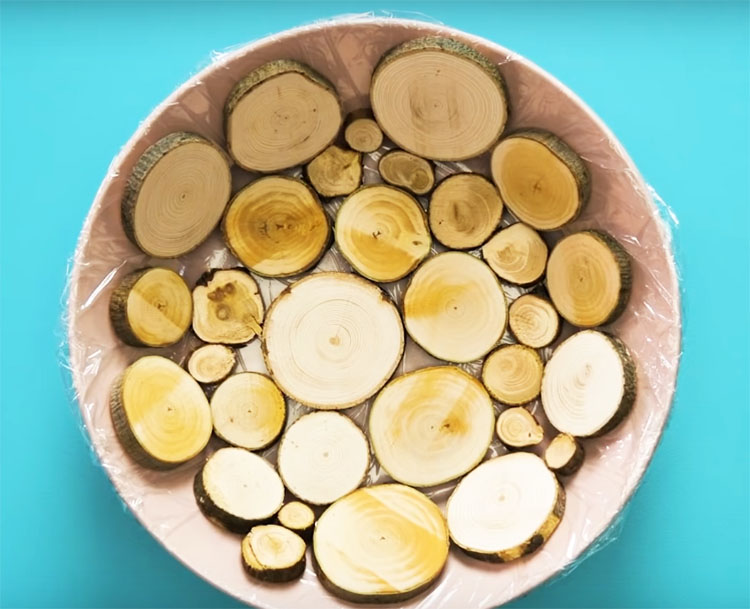 Уложите кусочки дерева в обёрнутую пищевой плёнкой посуду, используйте спилы разного размера