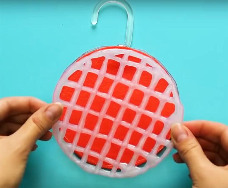 Сделайте две одинаковые сеточки, и на одной из них из того же клея приготовьте крючок. Проложите между сетками кусочек флиса или фетра и соедините их по краю