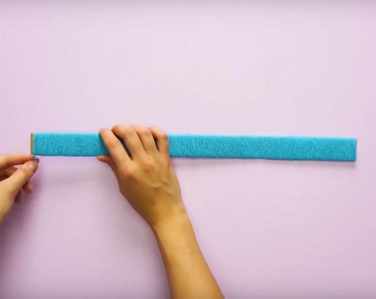 Приготовьте шаблон: это должна быть полоса картона шириной 3 см и длиной по ширине полотенца. Намотайте на заготовку нить, как показано на фото
