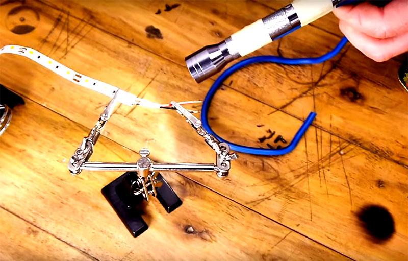 Примотайте фонарик к концу провода в двух местах. А сам провод согните так, чтобы на другом конце образовалось кольцо для устойчивой опоры на поверхности. Гибкое основание позволит расположить фонарик под нужным вам углом