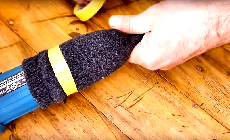 Возьмите носок, отрежьте самый кончик и через вилку и провод наденьте на рукоять болгарки. Зафиксируйте импровизированный фильтр с помощью изоленты или канцелярских резинок