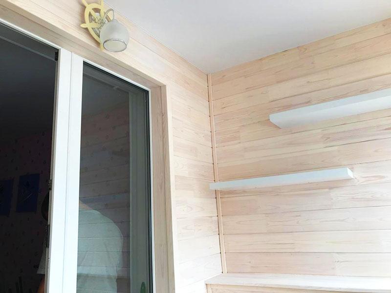 Сам балкон отделан плитами под шпон. А над спальным местом в шахматном порядке закреплены небольшие полочки
