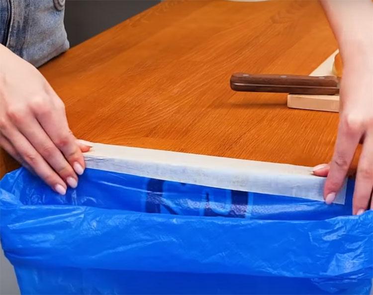 Возьмите мешок для мусора или полиэтиленовый пакет-майку и приклейте его к столу на свободную часть скотча
