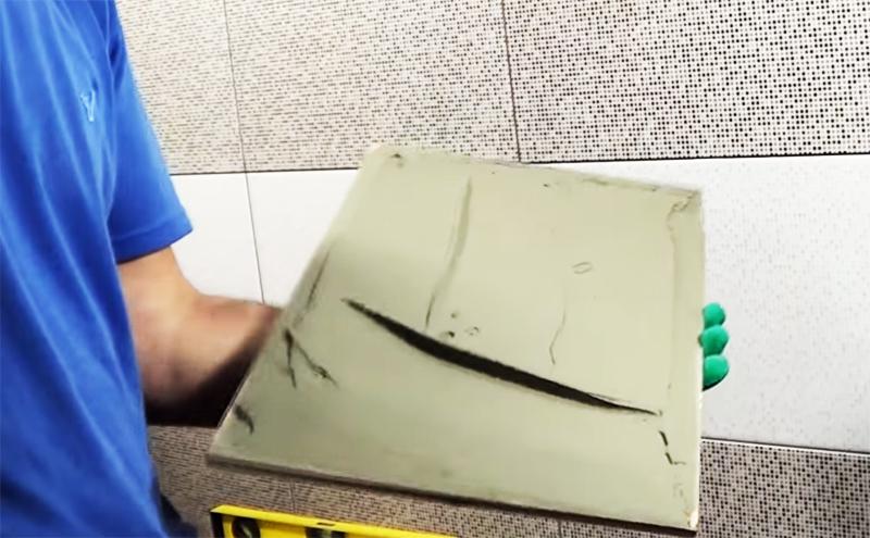 Клей наносится тонким слоем на внутреннюю поверхность плитки