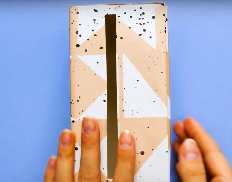 Оклейте коробочку плёнкой или цветной бумагой и сделайте в боковой стенке прорезь шириной примерно 1 см и длиной около 15 см