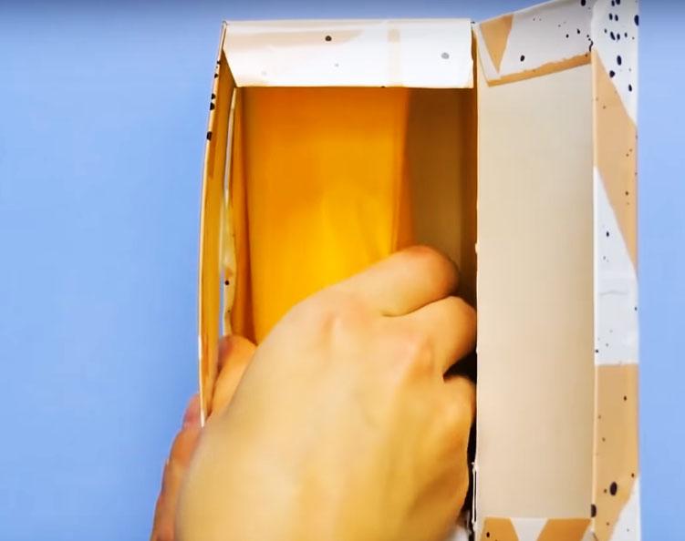 Уложите внутрь коробки рулон бумаги или свёрток с пакетами и протащите кончик через прорезь