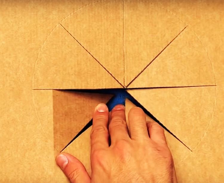 В нижней части коробки по центру начертите круг и сделайте прорези по радиусам так, чтобы можно было отогнуть их