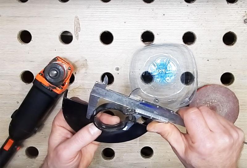 Следующий размер, который вам потребуется установить – это диаметр крепёжного хомута защиты инструмента. Вам нужно вырезать точно такое отверстие по центру донышка бутылки. Сделайте замер штангенциркулем и им же процарапайте круг на пластике, а потом вырежьте его ножницами. Можно обровнять край зажигалкой