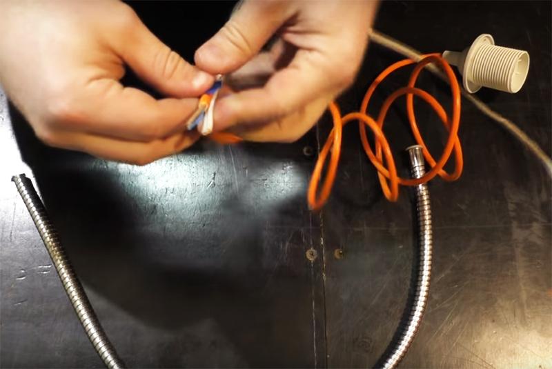 Извлеките содержимое гофры – это пластиковый шланг, он больше не понадобится. Вместо него внутрь нужно заправить два провода. Один из них – достаточно жёсткий, чтобы принимал и хорошо держал любую изогнутую форму, а второй – обычный электрический, через который будет подведено питание к лампе. Скрепите эти провода скотчем или изолентой и проденьте в гофру