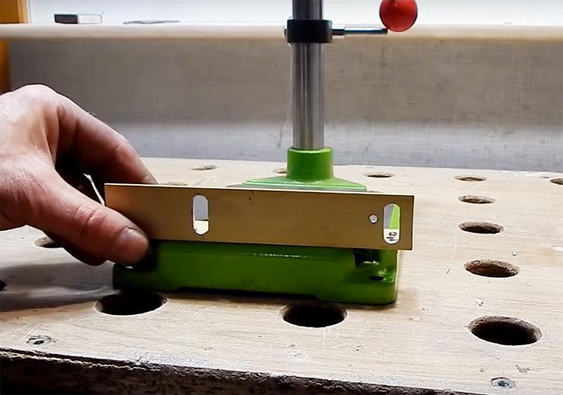 На другой стороне уголка следует сделать два продолговатых отверстия для фиксации шлифовальной машинки. Проще всего это сделать так: просверлить несколько отверстий в один ряд сверлом и потом соединить и отшлифовать их ножовкой