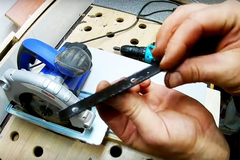 Для крепления стойки к подошве пилы потребуется полоска металла, в ней нужно сделать пару отверстий для фиксации рояльной петли. Эта полоса будет фиксироваться штатным крепежом параллельного упора