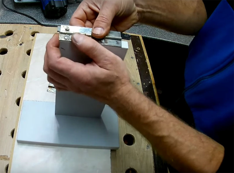Одну из рояльных петель крепим к панели и одновременно – к полоске металла для фиксации на дисковой пиле. Здесь используйте небольшие болты