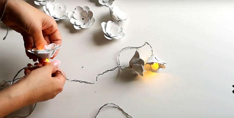 Насадите цветок из яичного лотка на лампочку гирлянды. Если отверстие небольшое, то даже никакого дополнительного крепления не требуется