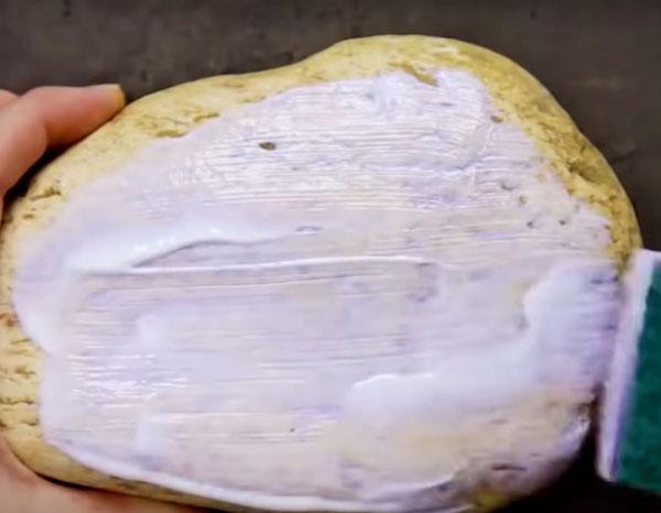 Нанесите слой клея на очищенную поверхность камня