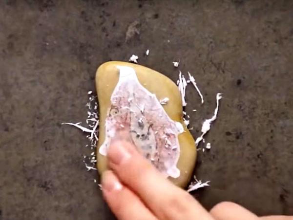 Затем мокрую бумагу начните тереть пальцами так, чтобы она скатывалась, пока сама картинка не останется на поверхности камня