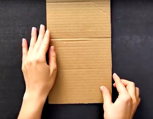 Приготовьте кусочек плотного картона для сохранения формы. Согните его пополам