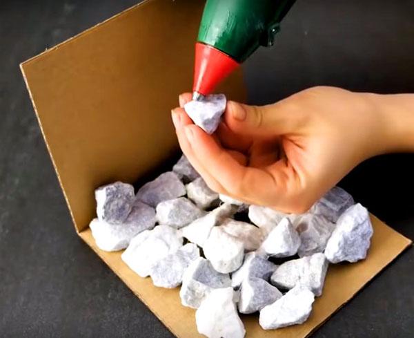 Начните укладывать камни, соединяя их между собой, но не скрепляя с картоном, он пригодится вам всего лишь в качестве шаблона