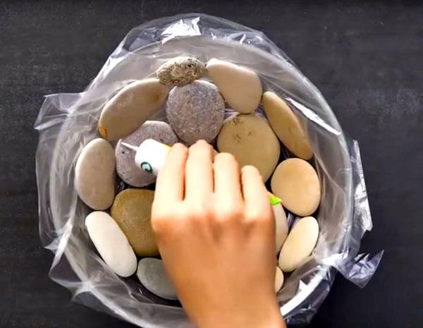 Уложите плоские камни по дну и стенкам чаши