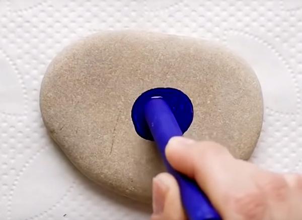 Пока камни горячие, а они довольно долго будут держать температуру, начните рисовать на них восковыми мелками концентрические круги