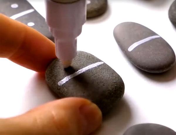 Маркером или акриловой краской и кистью сначала нарисуйте разделительную линию на каждом камне, а потом – точки