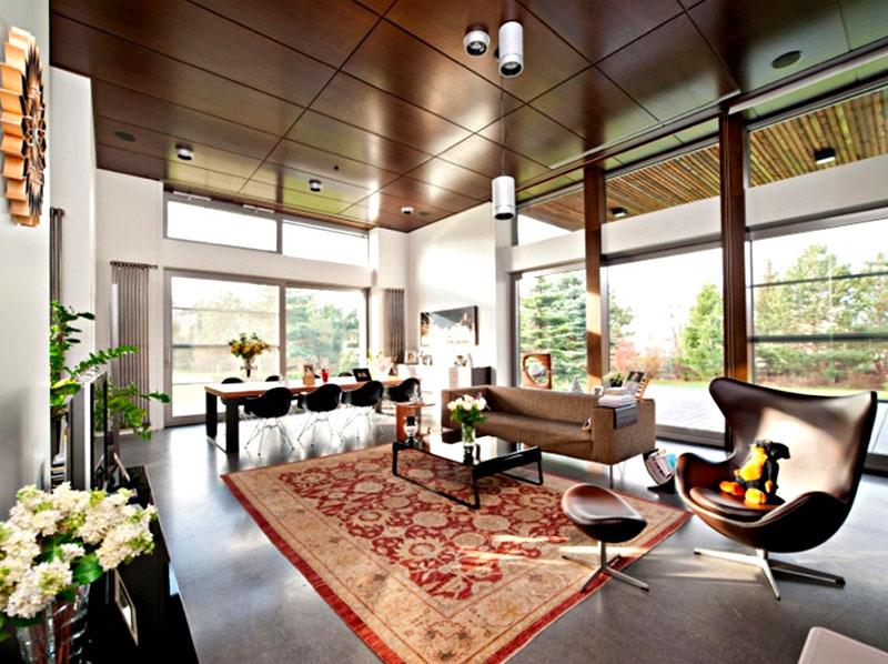 Возле панорамных окон организовали столовую зону с большим столом из массива и оригинальными креслами, обитыми натуральной кожей