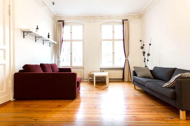 Высокие потолки, большие арочные окна и светлая отделка визуально делают комнату ещё просторнее