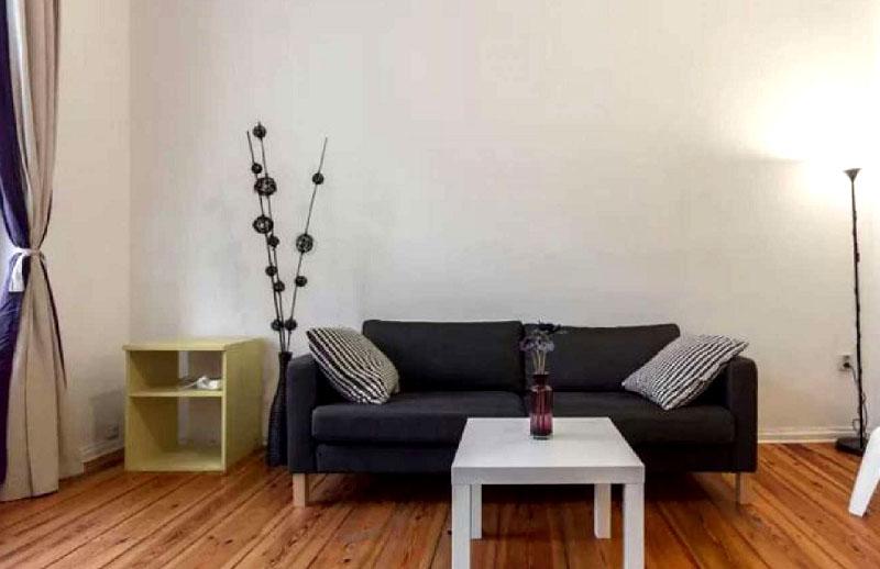 Строгий лаконичный декор в виде напольной вазы с искусственными ветками – это единственное украшение гостиной