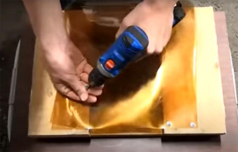 Для придания пластику нужной формы его один конец следует закрепить на ровной поверхности. Это может быть рабочий стол, верстак или заготовка с парой досок, как в этом случае