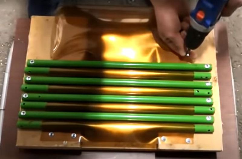 Чередуйте куски трубы поверх и снизу пластика, закрепляя их через одну так, чтобы исходный материал сгибался волнообразно под их давлением