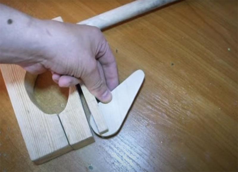 Подвижная часть прижимного механизма – это вот такой «медиатор» из фанеры. Желательно использовать фанеру 10 мм, тогда и паз в верхней части «прищепки» можно сделать такого же размера. Соответственно, если у вас фанера немного тоньше или деталь вырезана из дерева, то ширину верхнего паза нужно корректировать под нужные параметры