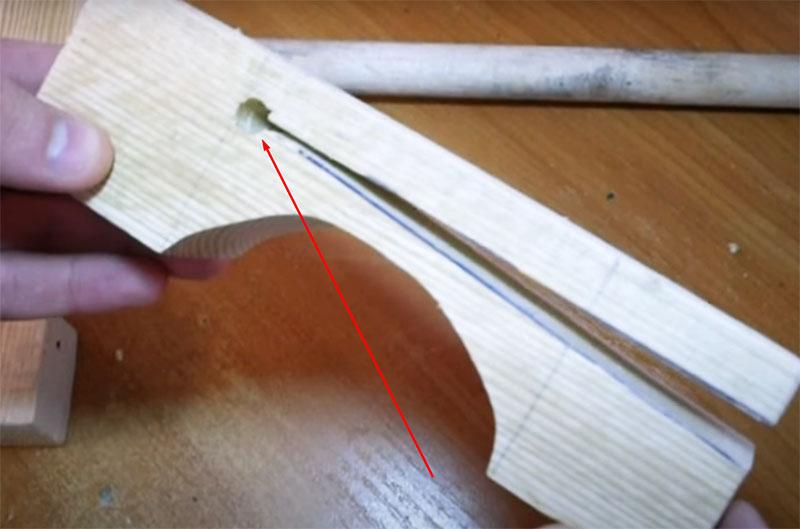 В основании v-образного пропила нужно высверлить круглое сквозное отверстие, которое необходимо для работы «прищепки»