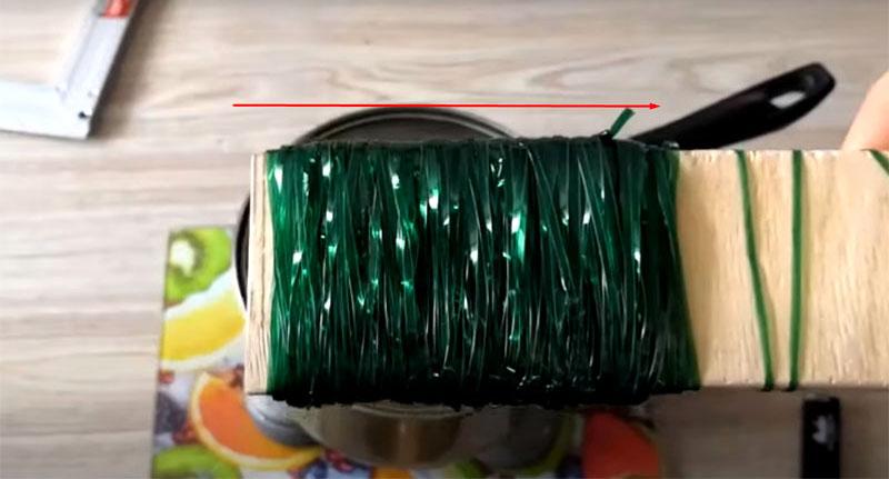 Намотайте пластиковую полоску на фанерную основу на ширину примерно 9 см. Используйте обе бутылки для намотки и концы полоски надёжно закрепите при обмотке