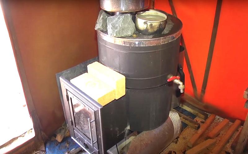 Печь следует установить на расстоянии от стенки баньки и желательно положить вокруг неё на землю негорючую подложку − остатки плитки или что-то подобное