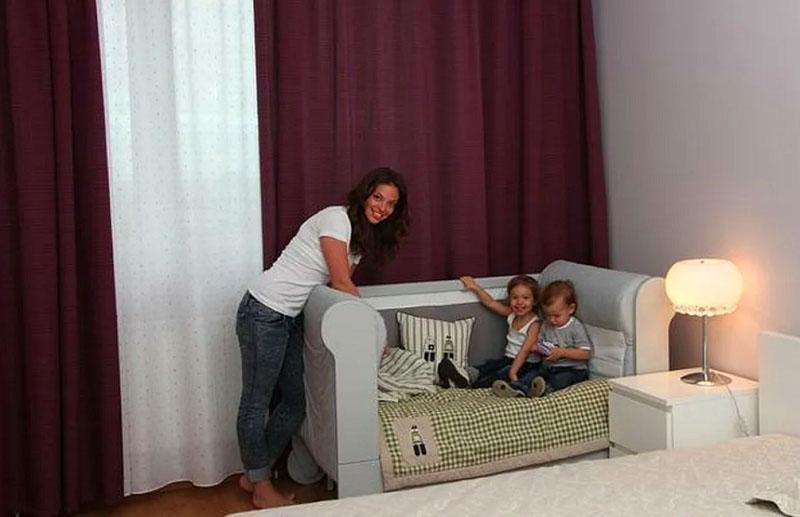Возле окна разместили небольшую детскую кроватку с высокой спинкой и боковинами, при желании её можно приставить к спальному месту родителей
