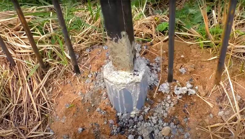 Вторая часть заливки с пластиковой трубой будет немного выступать над уровнем земли и пластик в этом случае надёжно защитит стальной профиль от контакта с атмосферными осадками и грунтовыми водами