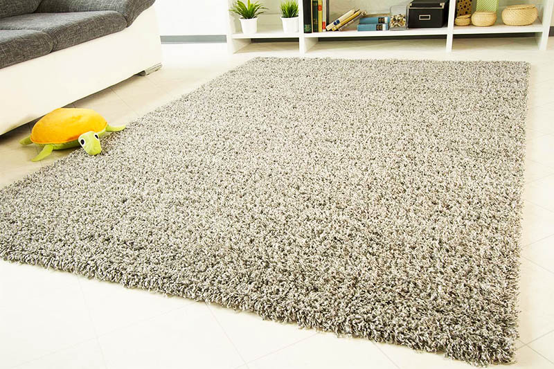 Выбирайте один большой ковёр, который будет лежать по центру комнаты. Если в квартире холодные полы, то в зонах, не закрытых основным ковром, вы можете добавить маленькие придверные коврики