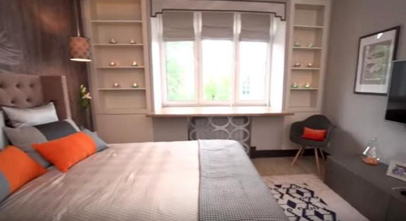Монохромную гамму разбавили декоративными подушками сочного апельсинового оттенка