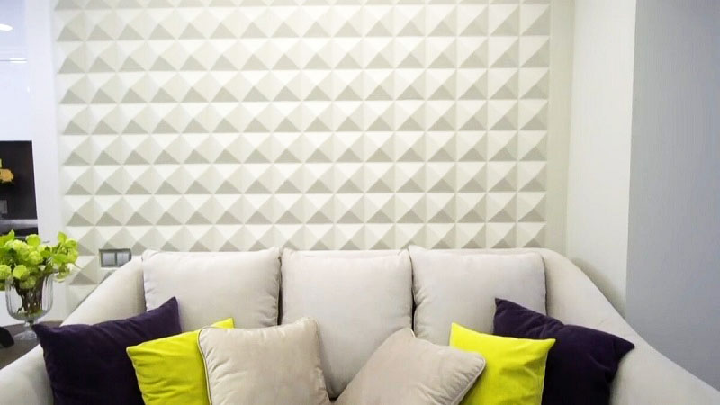 Яркие подушки освежают монохромное оформление гостиной