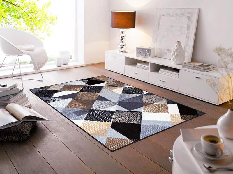 Идеальный вариант для гостиной – ковёр, выполненный в спокойных оттенках, с простым геометрическим рисунком, например в виде треугольников