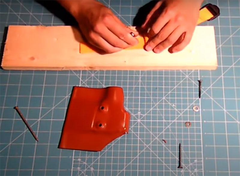 Для фиксации петли нужно сделать в чехле два отверстия. Их можно просверлить обычной дрелью, но возникает небольшой нюанс: шляпки болтов будут находиться на пути лезвия при вставлении в чехол и могут повредить режущую кромку. Чтобы этого не произошло, нужно не просто просверлить отверстия, но и создать выпуклый выход на наружную часть. Для этого вставьте в них саморезы и аккуратно нагрейте эти места феном, подтягивая крепёж наружу. Действуйте очень осторожно, чтобы не деформировать уже готовый чехол. Теперь, даже если вы вставите болты, шляпки утонут в приготовленных для них нишах