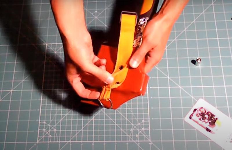 Петля из прочного материала крепится через пробитые в ленте люверсы в двух местах. Теперь вы можете продеть её на поясе или подвесить на ручку рюкзака