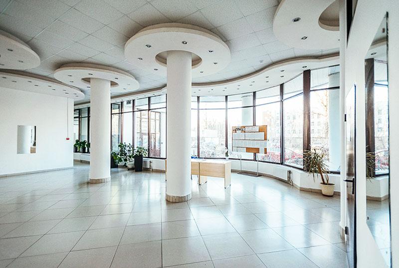 Просторный холл с колоннами оформлен в светлой гамме