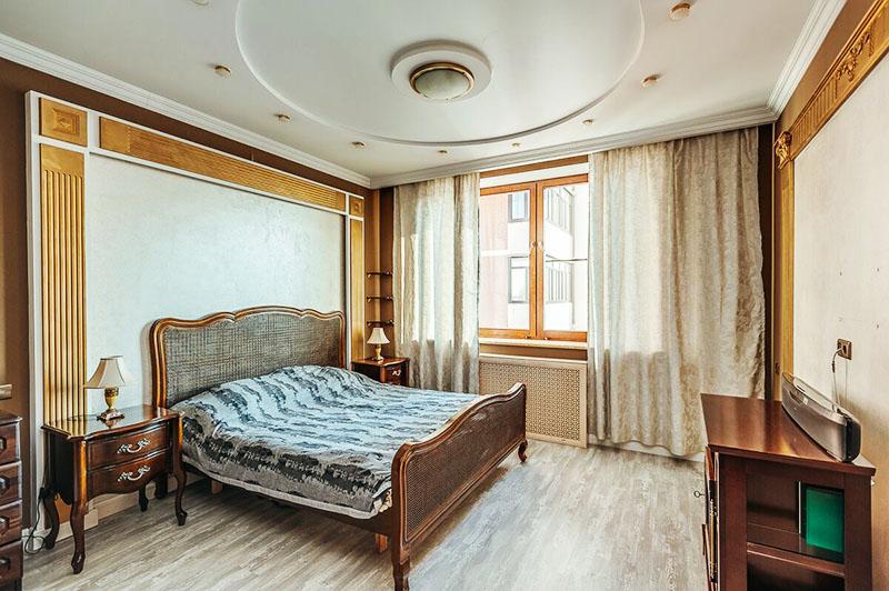 Напротив кровати поставили невысокий комод из массива, дверцы которого декорированы рейками в золоте