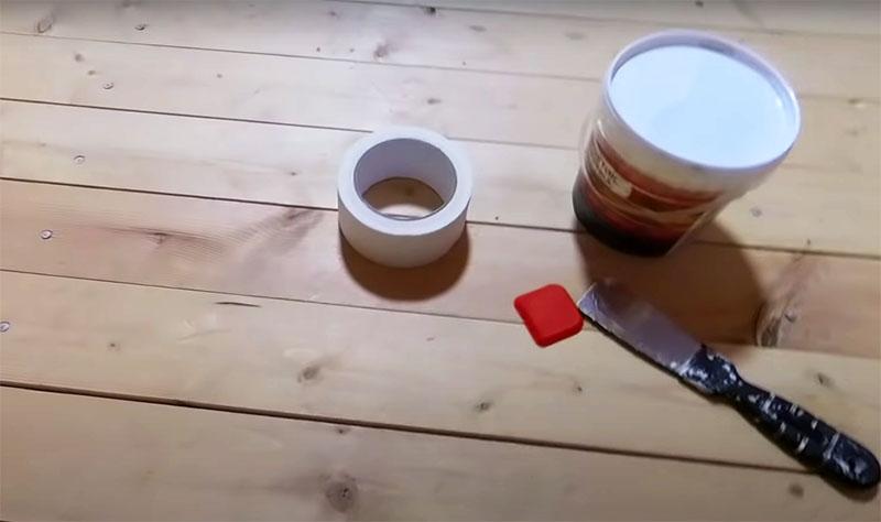 Приготовьте малярную ленту, узкий металлический шпатель и резиновый шпатель, который используют при укладке кафеля. Кроме того, вам нужно приобрести герметик по дереву подходящего для ваших полов тона