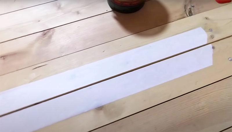 Скотч нужно наклеить вдоль щели с двух сторон на доску. Малярный скотч в этой ситуации защитит остальную поверхность настила