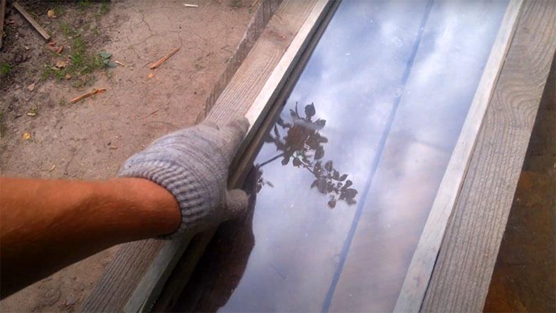 После установки стекла нужно закрепить его вторым рядом реек. Теперь рейки удобнее будет просто прибить парой гвоздей на каждой стороне. Если стекло со временем разобьётся, его будет легко заменить, просто вынув гвозди