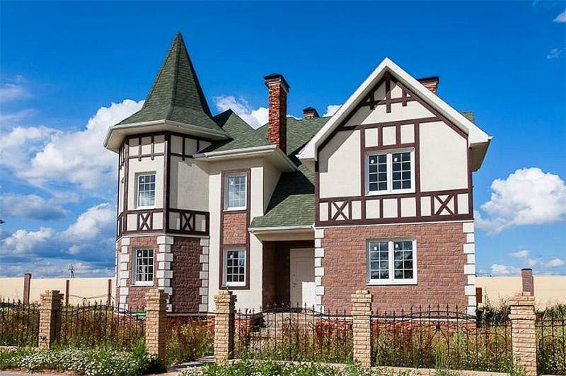 Декоративная плитка на фасаде идеально сочетается с зелёной черепицей и светлой покраской второго этажа